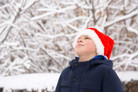 boy wearing a Santa hat outdoors in winter