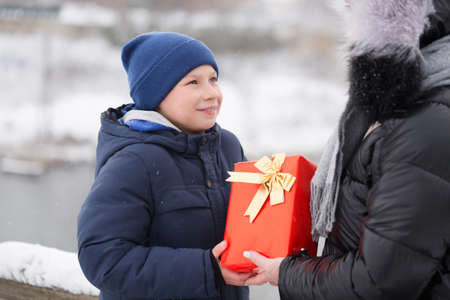 Boy gives mom a gift, outdoors in winter