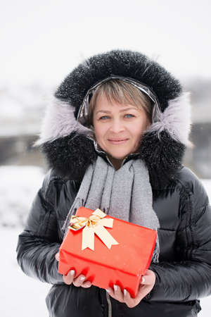 Woman in a jacket with a box in her hands outdoors