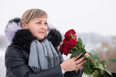 Woman with red roses outdoors in winter Archivio Fotografico
