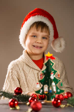 Boy in santa hat decorates wooden vintage christmas tree with toys