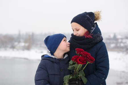 The boy gives the girl red roses Archivio Fotografico