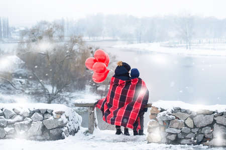 Children with balloons admire the scenery while wrapped in a blanket outdoors