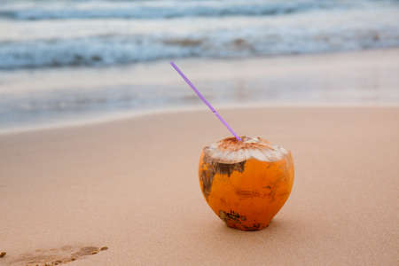 coconut with a straw on the sand by the ocean, summer background