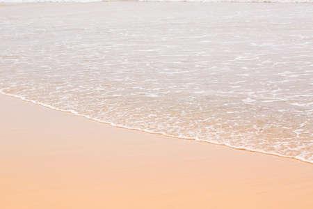 Golden wet sand in the ocean, summer background