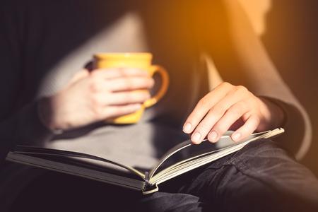 Nahaufnahme der weiblichen Hände, die offenes Buch halten. Frau liest Buch.
