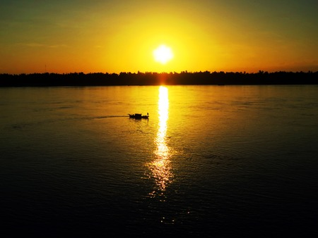 Silhouette of boat at sunset on the Mekong river in Kratie, Cambodia