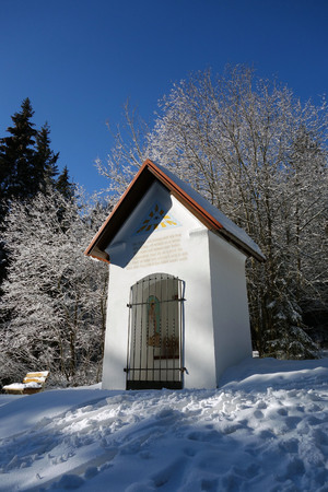 A chapel in the snow under a blue sky on schoeckl, Austria Stock Photo