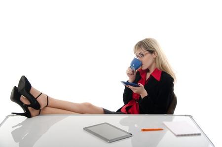 feet on desk: office worker drinking tea feet on the table