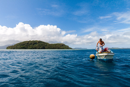 Pohnpei, Micronesia - Dec 27,2011: a local Micronesian in a boat man pulls a buoy out of the water with Pohnpei island in the background, Caroline islands, Federated States of Micronesia (FSM) Editorial