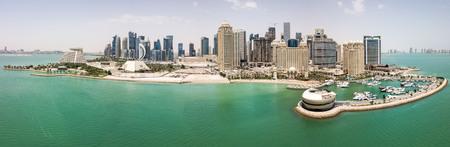 El horizonte de Doha, Qatar. Moderna y rica ciudad de rascacielos del Medio Oriente, vista aérea cuando hace buen tiempo, al mediodía, durante el verano caluroso y seco, con vista al puerto deportivo y la playa del Golfo Pérsico / Golfo Arábigo Foto de archivo