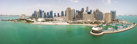 The skyline of Doha, Qatar. Modern rich middle eastern city of skyscrapers, aerial view in good weather, midday, during hot dry summer, with view of marina and beach of Persian Gulf/Arabian Gulf