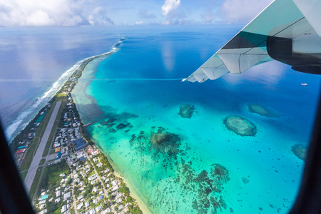 Tuvalu under the wing of an airplane. Aerial view of Funafuti atoll and the airstrip of International airport in Vaiaku. Fongafale motu. Island nation in Polynesia, South Pacific Ocean, Oceania.