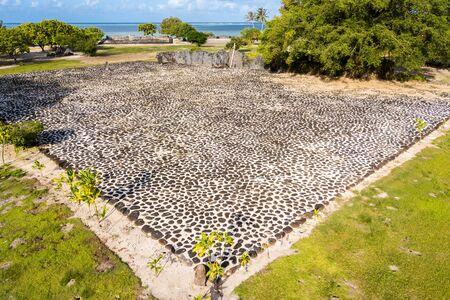 Marae Taputapuatea temple complex. Ancient stone carved sacred tiki (idol statue) and ahu altar. Raiatea island. Leeward / Society Islands, French Polynesia, Oceania, South Pacific Ocean. Aerial view. Фото со стока