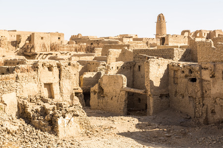 Ruins of ancient arab middle eastern old town built of mud bricks, old mosque with minaret. Al Qasr, Dakhla Oasis, Western Desert, New Valley Governorate, Egypt, Africa.