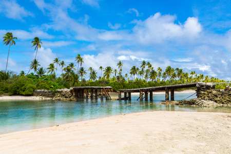 Broken bridge under palm trees between islets over lagoon, North Tarawa atoll, Kiribati, Micronesia, Gilbert islands, Oceania, South Pacific Ocean. Infrastructure problems of small island nations.