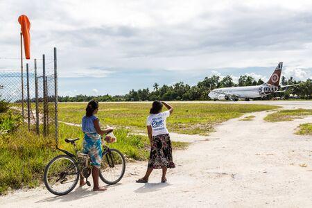 Bonriki airport runway, departing Fiji Airways Boeing 737. Local teenage girls with a bicycle looking at a departing airplane, South Tarawa atoll, Kiribati