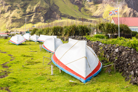 Countryside grass street with a row of drying overturned boats. British Governor flag flying. Edinburgh of the Seven Seas town, Tristan da Cunha, the most remote inhabited island, South Atlantic Ocean Archivio Fotografico