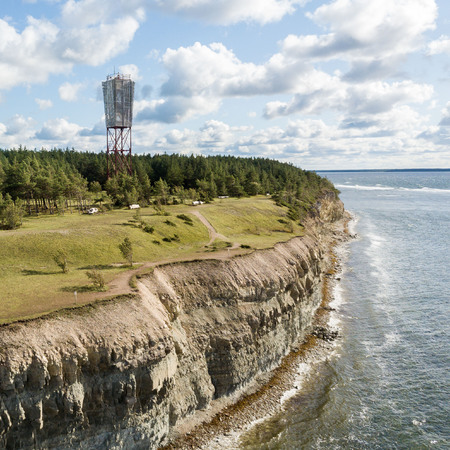 Panga coastal cliff and lighthouse (Panga pank, Mustjala cliff), northern shore of Saaremaa island, near Kuressaare, Estonia. North-Estonian limestone escarpment, Baltic Klint. Bird eye aerial foto.