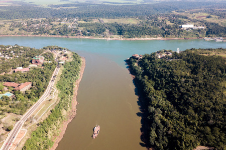 Triple Frontier, tri-border junction of Paraguay, Argentina and Brazil. Iguazú and Paraná rivers confluence. Cities Ciudad del Este; Puerto Iguazú, Foz do Iguaçu. Aerial drone photo. Two color river
