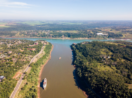 Triple Frontier, tri-border junction of Paraguay, Argentina and Brazil. Iguazú and Paraná rivers confluence. Cities Ciudad del Este; Puerto Iguazú, Foz do Iguaçu. Aerial drone photo. Two color river