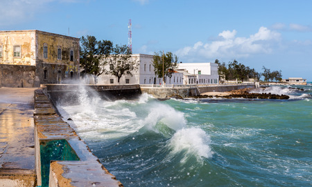 Ocean waves crash over a seawall to seafront embankment. Mozambique island (Ilha de Mocambique), Indian ocean coast, Moçambique. Mozambique Channel, Mossuril Bay, Nampula Province. Portuguese Africa