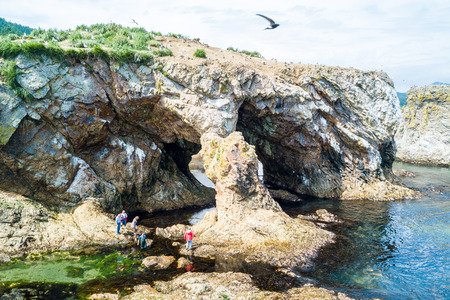 Tourists/trekers evaluating natural arch. Aerial drone photo of cape Ptichiy, Sakhalin island, Russia (near by cape Velikan). Surrealistic landscape of natural arches created by wind and sea erosion.