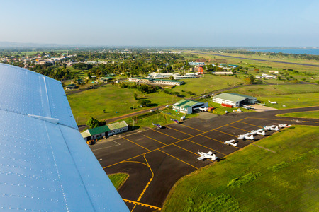 Air travel in Fiji, Melanesia, Oceania. View of hangars, helicopters and small planes on Nausori Suva International Airports apron, Viti Levu island, from a window of a small airplane during take off
