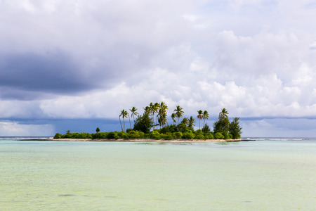 A small islet (motu) overgrown with palm forest somewhere in the lagoon of South Tarawa atoll in bad cloudy weather, Kiribati, Gilbert islands, Micronesia, Oceania. Wet rainy season on Kiribati. Banco de Imagens