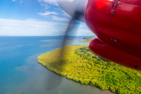 Air travel in Fiji, Melanesia, Oceania. View of a green remote tropical island from a window of a small turboprop propeller red engine airplane flying over blue azure turquoise lagoon, near Viti Levu.