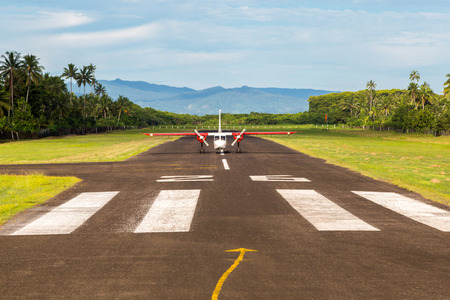 Air travel in Fiji, Melanesia, Oceania. A small propeller airplane just landed to a remote airstrip overgrown with palms, lost in jungle Levuka town, Ovalau island. Viti Levu big island in background.