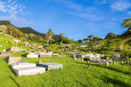 Ovalau, Fiji - Jan 09 2015: Hillside cemetery with summer lush green lawns, palms, blue sky and old gravestones, Ovalau island, Lomaiviti archipelago, Fiji, Melanesia, Oceania, South Pacific Ocean. 新聞圖片