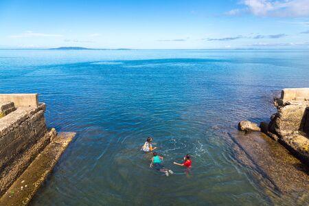 Levuka town, Fiji - Jan 9 2015: Indigenous fijian Melanesian kids are swimming off the embankment, Ovalau island, Lomaiviti archipelago, Fiji, Melanesia, Oceania, South Pacific Ocean. View of Wakaya.