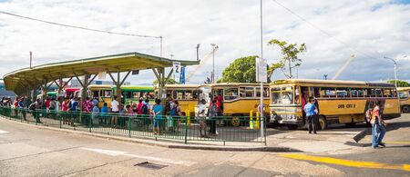 Suva, Fiji - Dec 31 2014: Busy central bus station in Suva city center downtown full of hurrying passengers and authentic old-timer yellow buses, Viti Levu island, Fiji, Melanesia, Oceania. Terminal 2