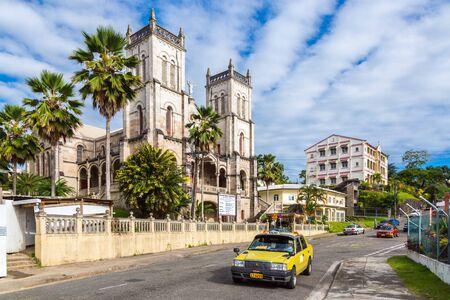 Suva, Fiji - Dec 31 2014: Sacred Heart Cathedral of Suva, Archdiocese of Suva. Roman Catholic Church. Vibrant Suva downtown traffic with a yellow taxi cab on Pratt Street.