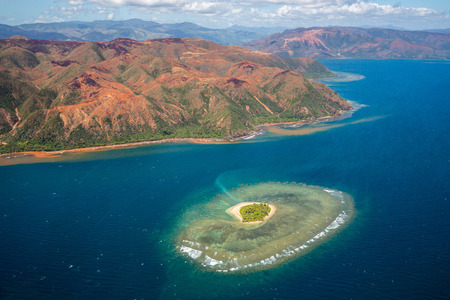 A small atoll islet with heart shaped coral reef off the east coast of Grande Terre island of New Caledonia, French overseas collectivity. Red green mountains hills full of nickel ore near Nakéty
