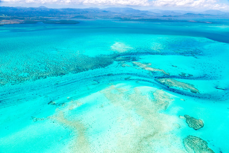 Aerial view of idyllic azure turquoise blue lagoon of West Coast barrier reef, with mountains far in the background, Coral sea, New Caledonia island, Melanesia, South Pacific Ocean.