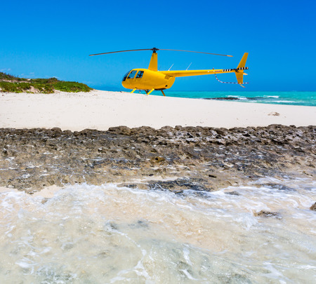 A yellow helicopter landed on idyllic empty sandy beach of remote island, azure turquoise blue lagoon in background, West Coast barrier reef, Coral sea, New Caledonia, Melanesia, South Pacific Ocean