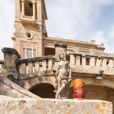 Paceville, Malta - Jun 18 2010: Focus on a can of Kinnie with a historic mansion and an ancient sculpture in the background. Maltese bittersweet soft drink brewed from bitter oranges and wormwood. Editoriali