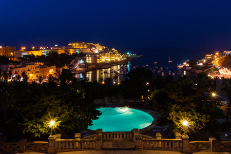 View of St. Georges Bay seafront lights by night, with a blue luxury swimming pool and boats and yachts anchored. St Julians (San Giljan), Central Region, Malta. Evening in Paceville district Banco de Imagens