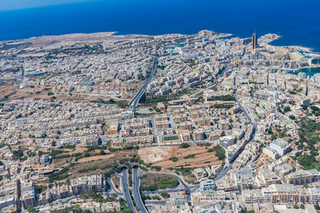 Aerial view of urban Malta. Tunnel on highway 1 under Ta Giorni town and Paceville district, parts of St. Julians (San Giljan) city from above. Blocks of apartment buildings, sleeping quarters Banco de Imagens