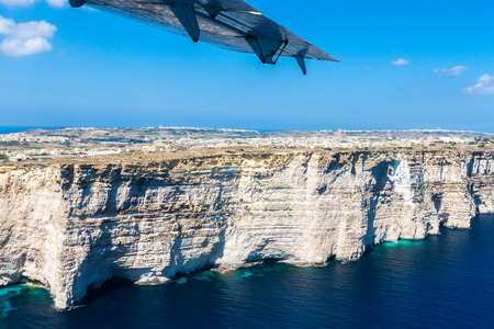 Gozo island from above, under the wing of a small plane. Aerial view of Gozo, Malta. The Rotunda of Xewkija (Casal Xeuchia) is the largest in Gozo island and its dome dominates the village