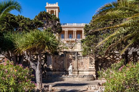 St. Julian's, Malta - Jun 18 2010: 1920s art nouveau mansion Villa Rosa built in park in St. Julian's town by architect Andrea Vassallo, Malta, reflects in azure swimming pool.