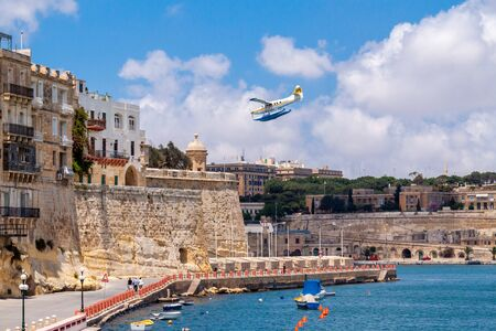 Valetta, Malta - Jun 20, 2010: Harbour Air seaplane De Havilland Canada DHC-3 Turbine Otter 9H-AFA is water landing in the Grand Harbour, with Valletta old fortification walls in the background. Editorial