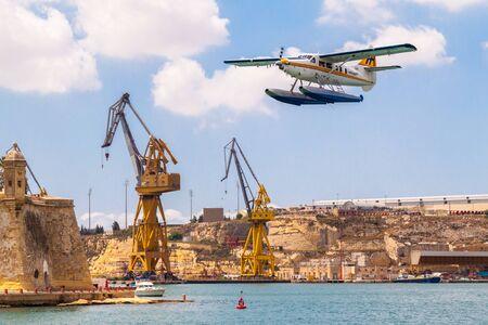 Valetta, Malta - Jun 20, 2010: Harbour Air seaplane De Havilland Canada DHC-3 Turbine Otter 9H-AFA is taking off in the Grand Harbour, Senglea fortification walls and Malta shipyard in the background. 新聞圖片