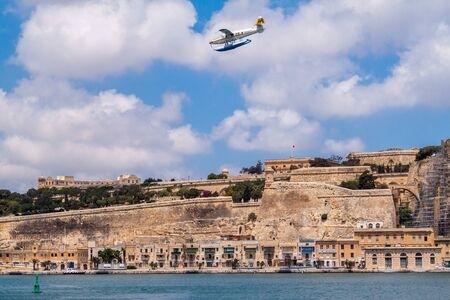 Valetta, Malta - Jun 20, 2010: Harbour Air seaplane De Havilland Canada DHC-3 Turbine Otter 9H-AFA is water landing in the Grand Harbour, with Valletta old fortification walls in the background. 新聞圖片