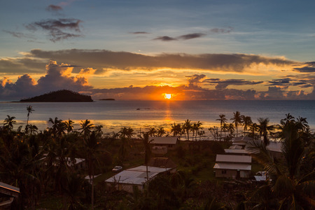 Early morning and sunrise over Pacific Ocean in Mata-Utu village, the capital of Wallis and Futuna territory (Wallis-et-Futuna), French overseas island collectivity. Downtown is overgrown with palms Imagens