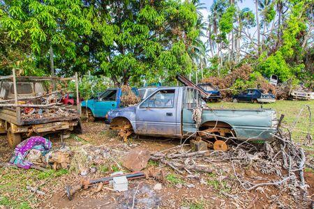 Vailala, Wallis and Futuna - Jan 6 2013: Automotive graveyard, car cemetery yard, abandoned car junkyard under palm trees on a remote island of Uvea, Wallis and Futuna. Ecological problems of islands. Editorial