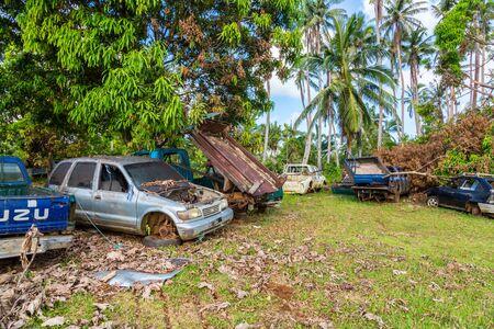 Vailala, Wallis and Futuna - Jan 6 2013: Automotive graveyard, car cemetery yard, abandoned car junkyard under palm trees on a remote island of Uvea, Wallis and Futuna. Ecological problems of islands. 新聞圖片