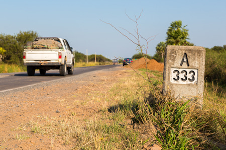 A pickup truck hurrying by A333 milestone - kilometre mark - along the highway number 9 Ruta Transchaco, Gran Chaco, Paraguay, Latin America, South America. Archivio Fotografico